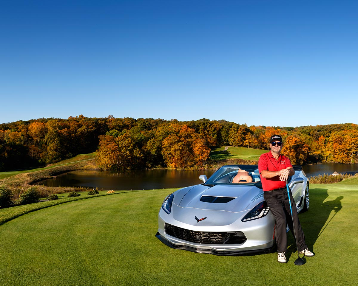 A man leans against a nice sports car parked on a golf course with autumn colored trees in the distance